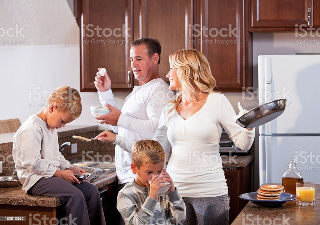 Family in kitchen making breakfast stock photo