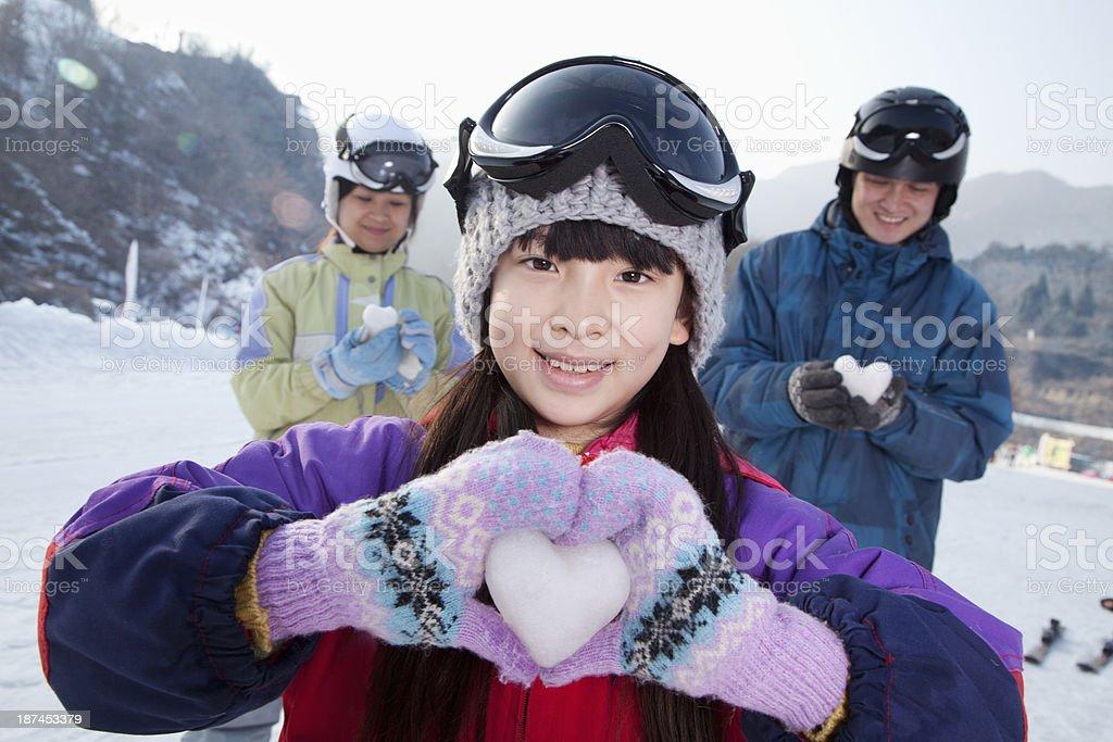 Family in Ski Resort, Daughter Showing Snow Heart stock photo