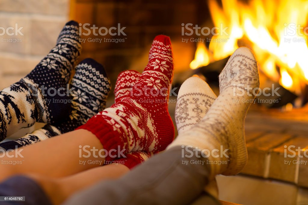 Family in socks near fireplace in winter or christmas time stock photo