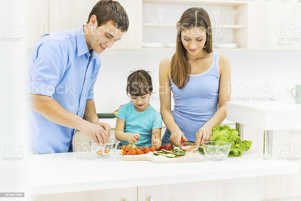 Family in the kitchen preparing food together. royalty-free stock photo