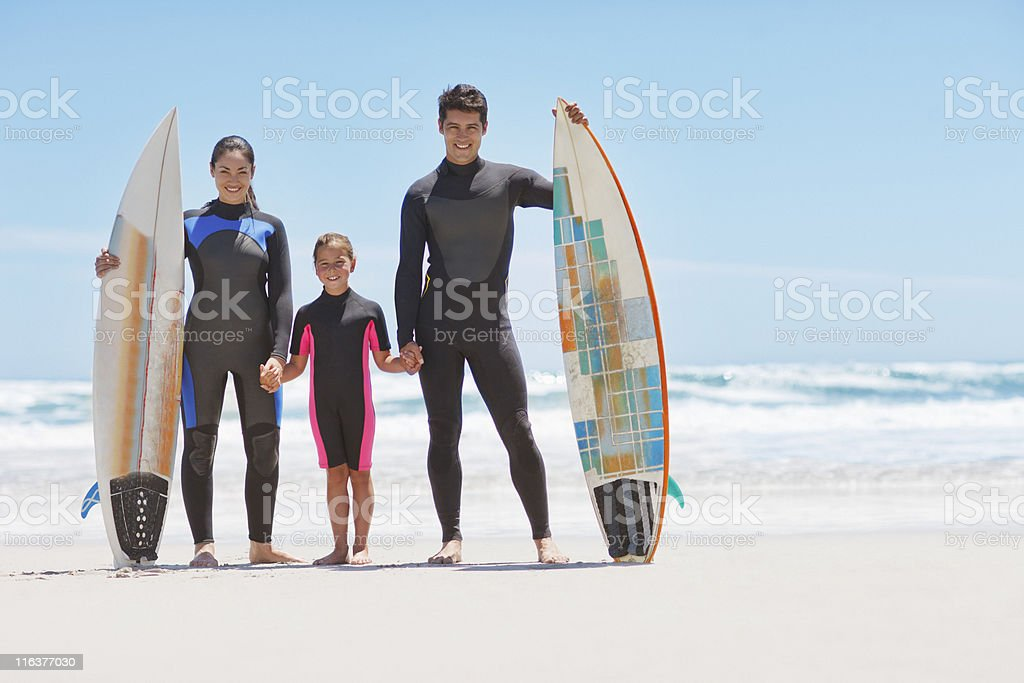Family in wetsuits with surfboards on beach royalty-free stock photo