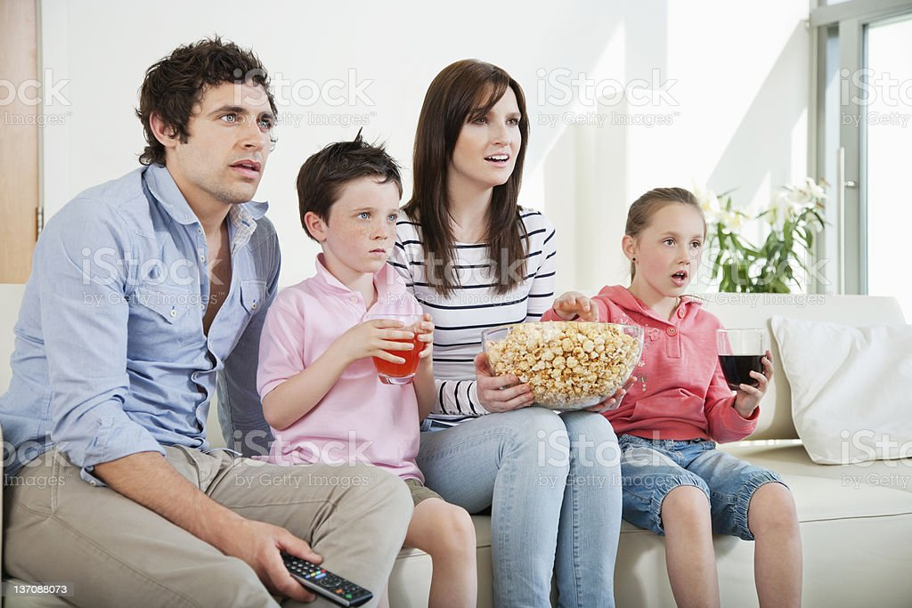 Family intently watching movie on sofa royalty-free stock photo