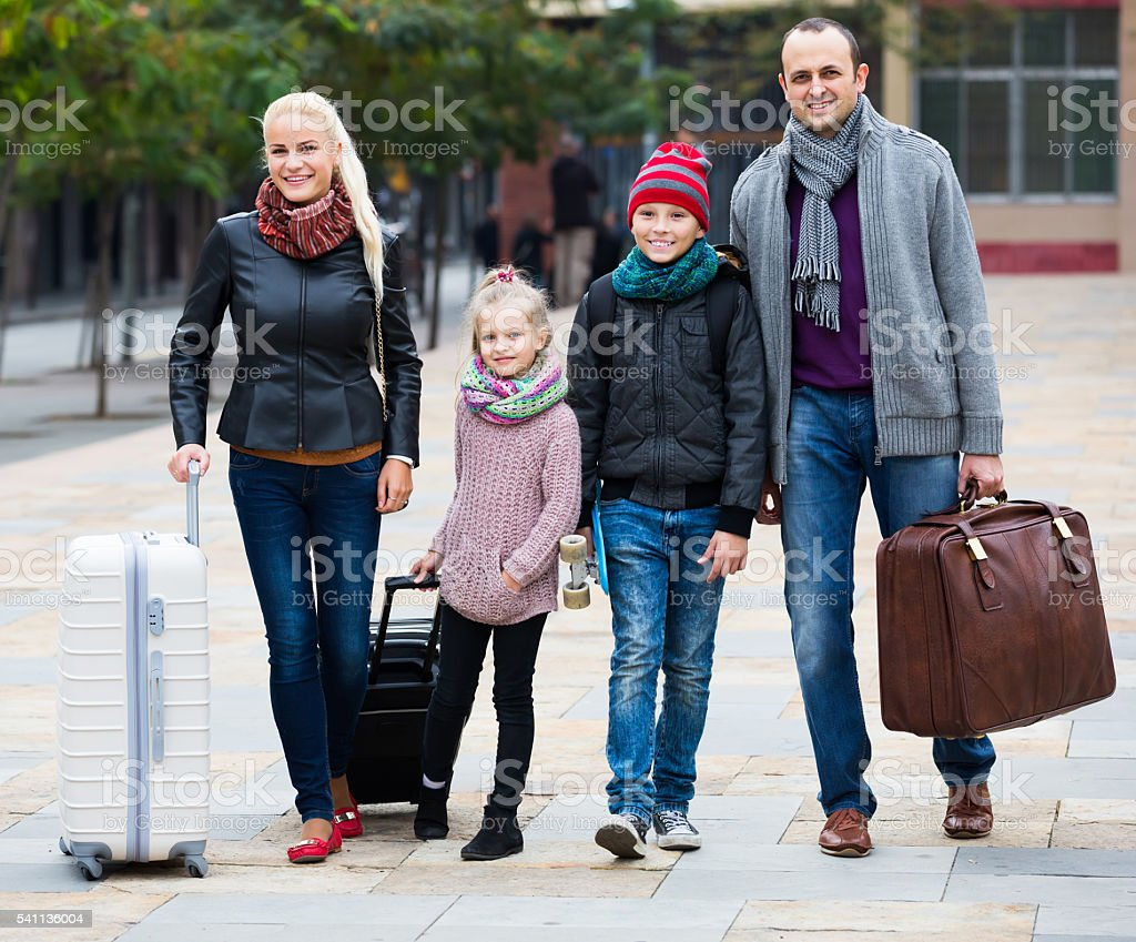 Family journey: spouses with children walking and luggage stock photo