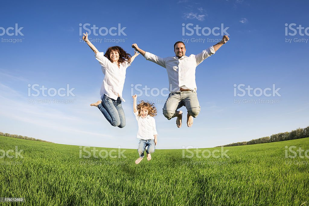 Family jumping in green field at summer vacation stock photo