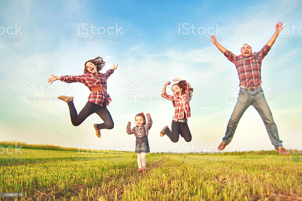 family jumping in the field. stock photo