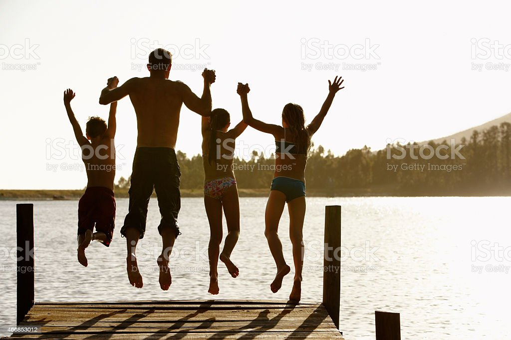 Family Jumping Off A Jetty stock photo