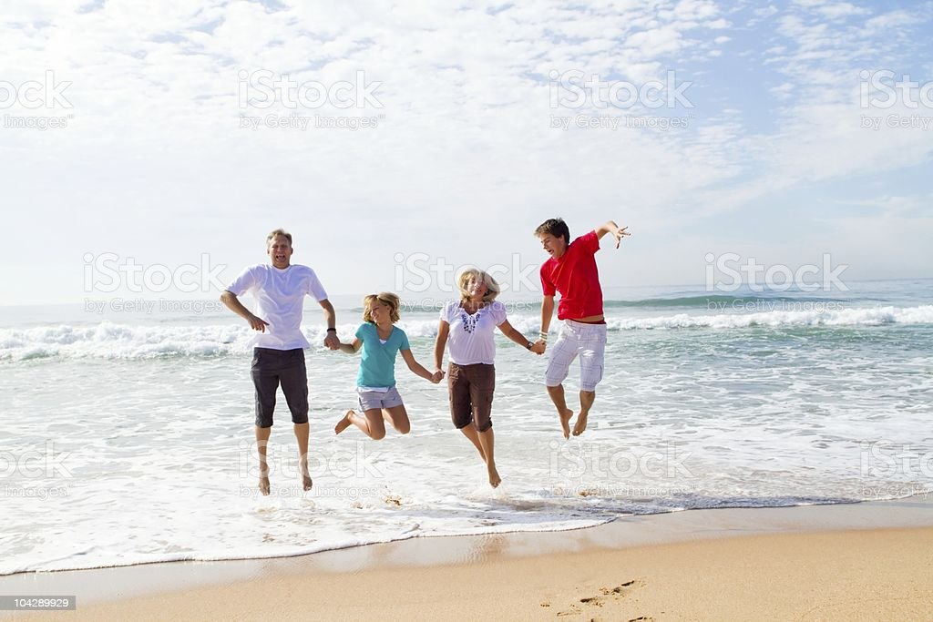 family jumping on beach royalty-free stock photo