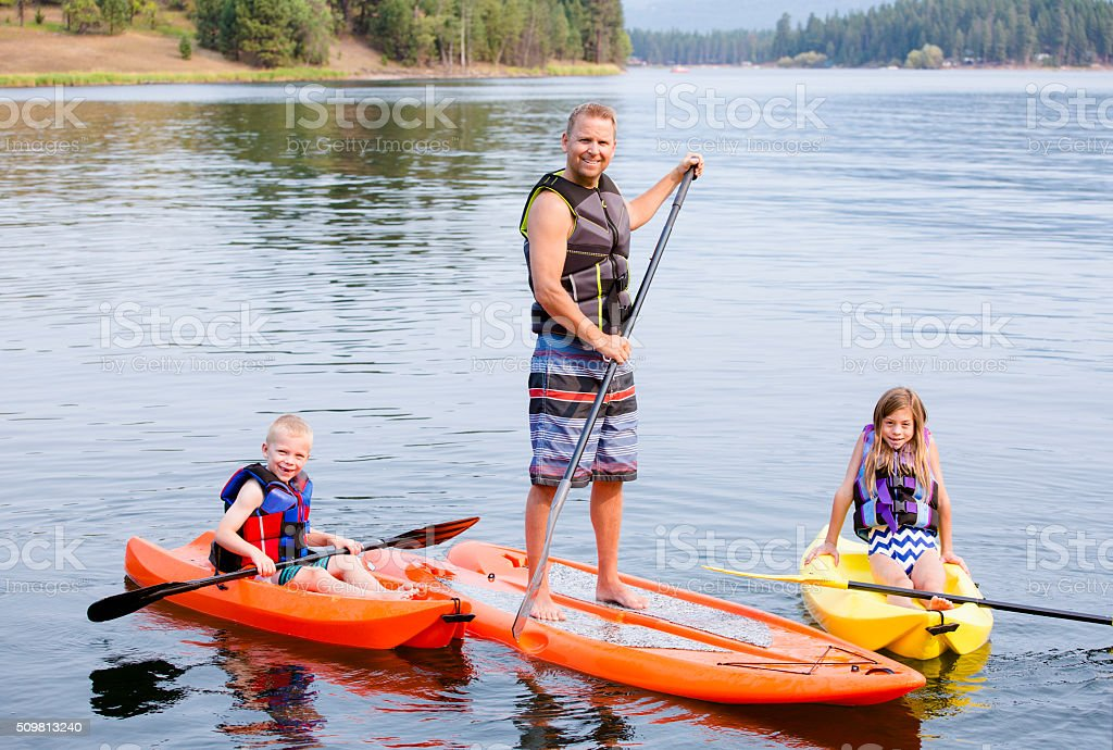 Family kayaking and paddle boarding together stock photo