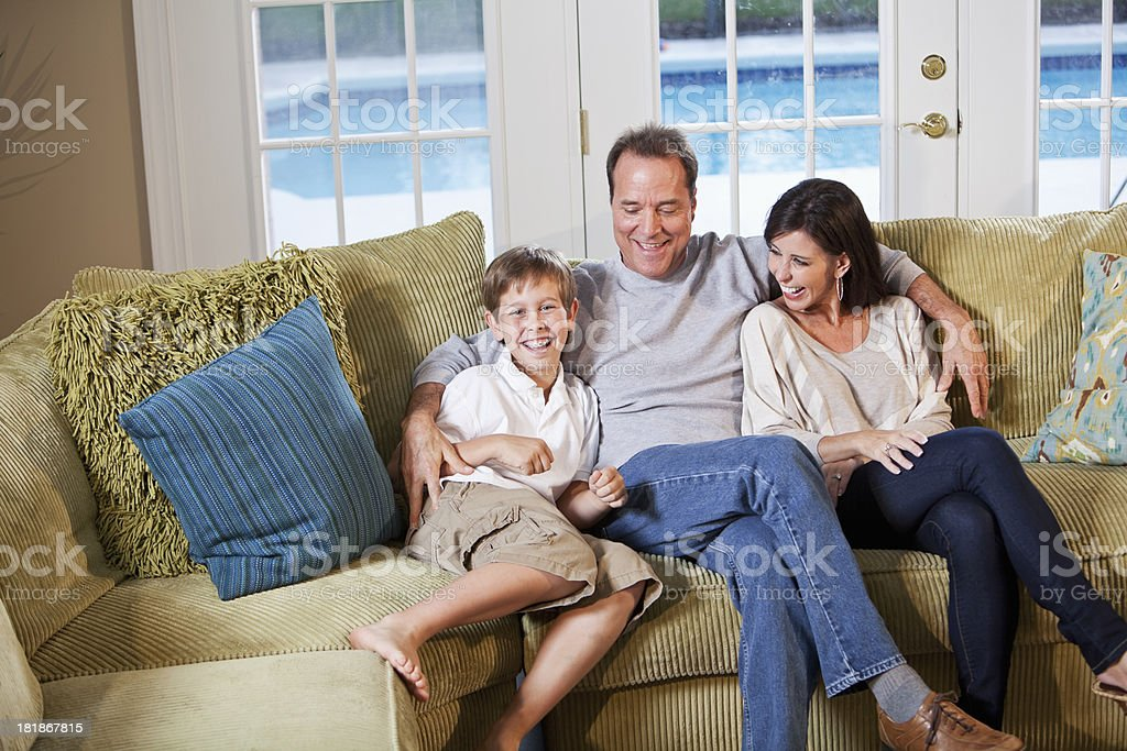 Family laughing on couch stock photo
