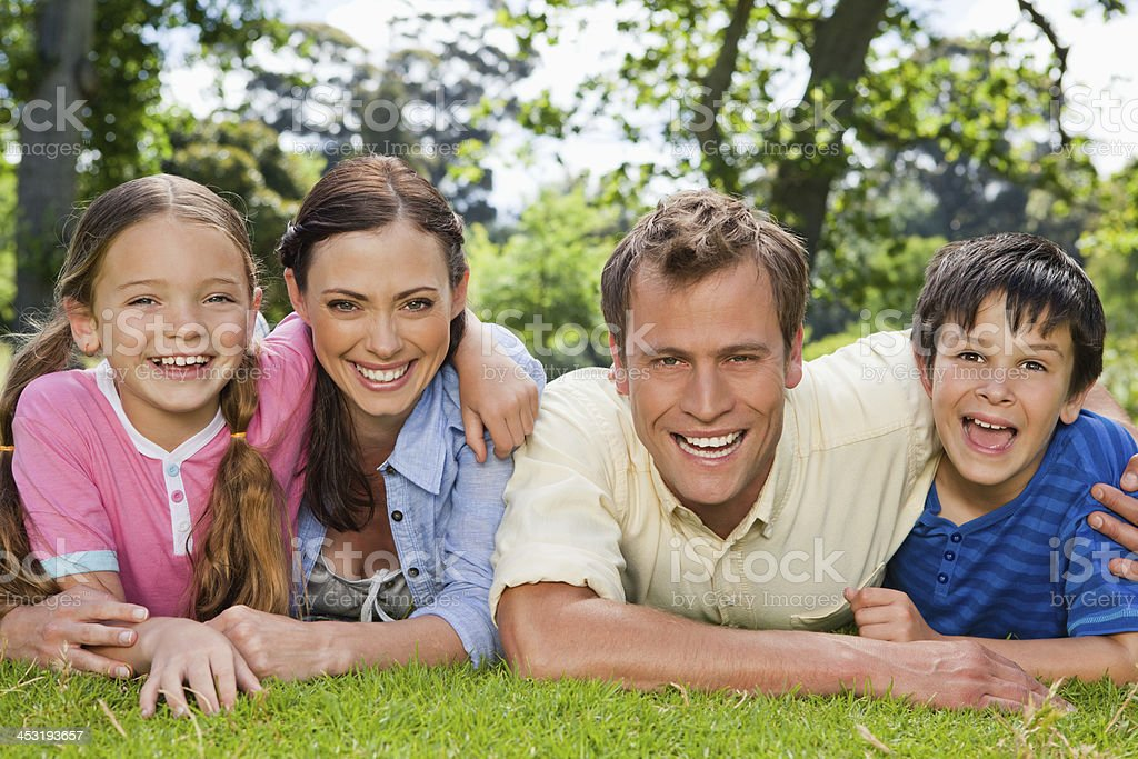 Family laughing together while lying in a park royalty-free stock photo