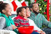 Family laughs while watching Christmas movie