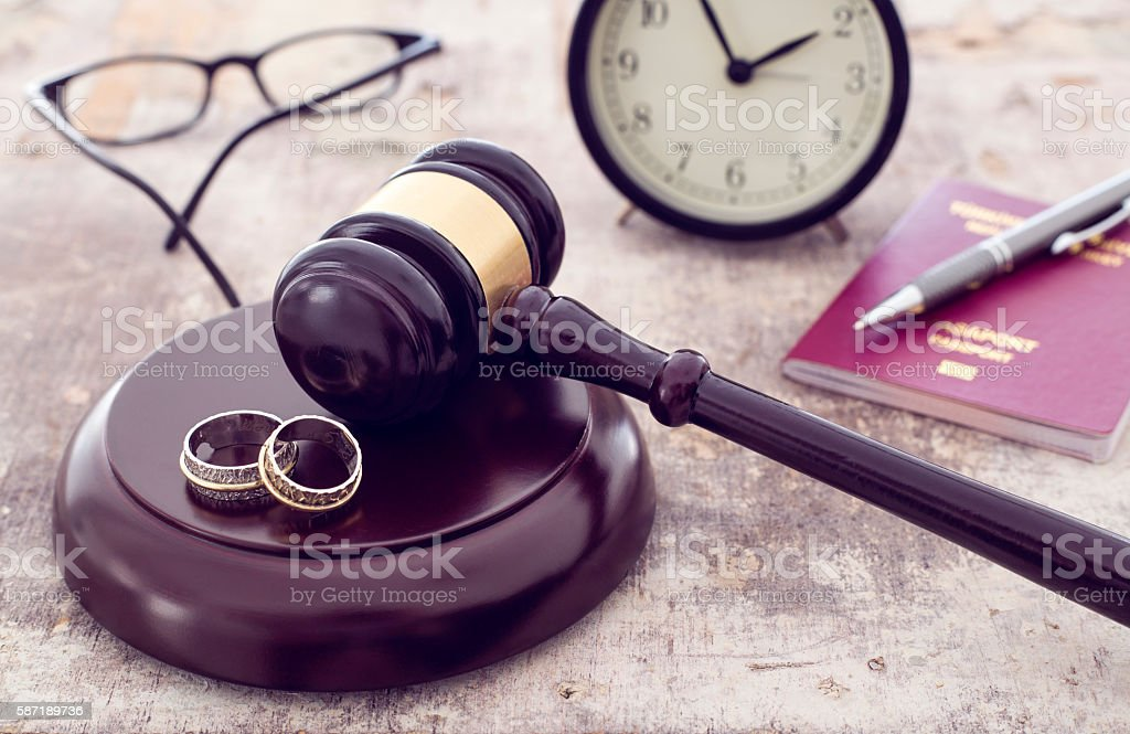 Family law concept, gavel, rings and money on wooden table stock photo