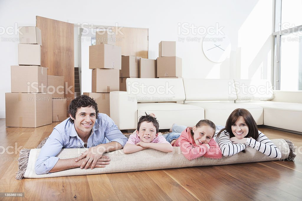 Family laying on carpet in new home stock photo