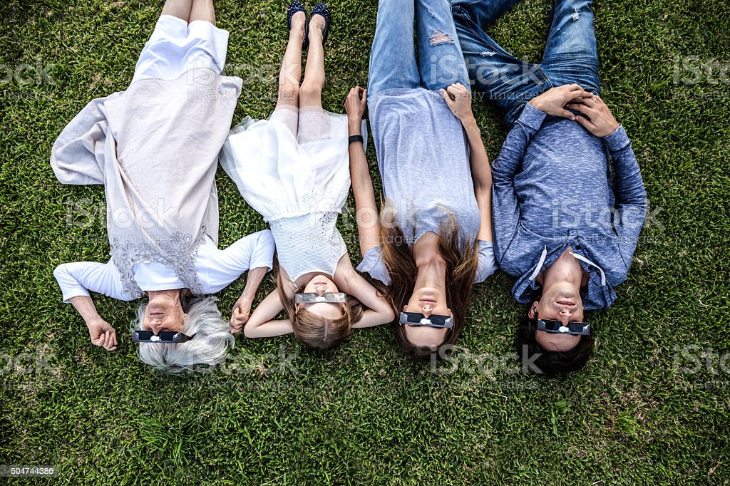 Family laying on the grass looking at Solar Eclipse stock photo