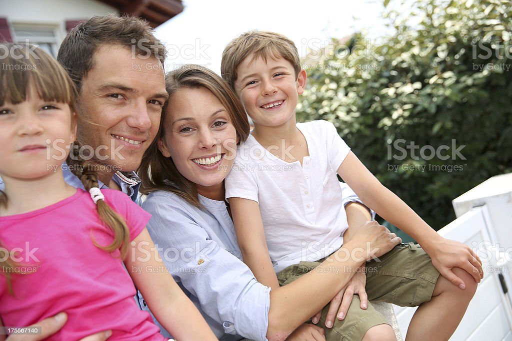 Family leaning on fence in front of their home royalty-free stock photo