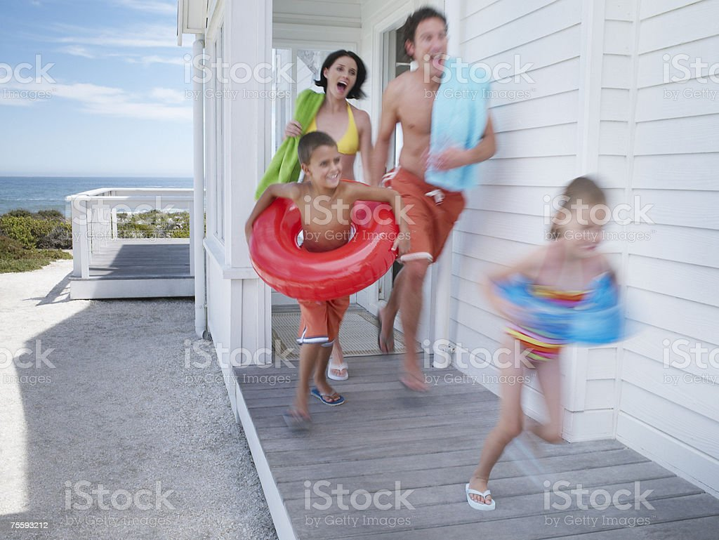 A family leaving their beach house with swimming gear royalty-free stock photo