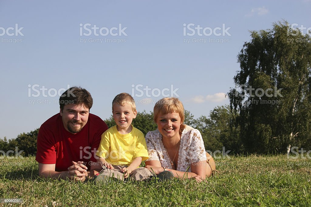 family lies on grass royalty-free stock photo