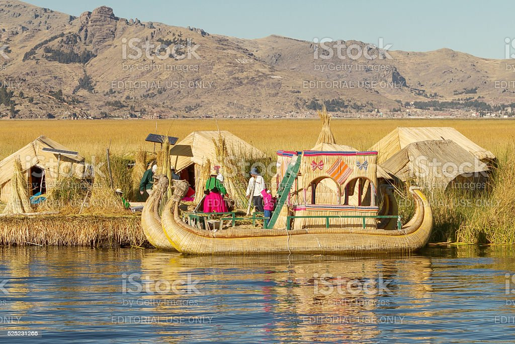 Family living on floating reed islands of Uros, Lake Titicaca stock photo
