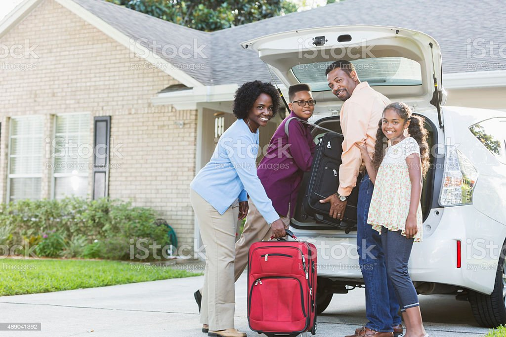 Family loading luggage into car going on vacation stock photo