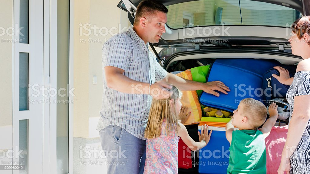 Family loading luggage into car stock photo