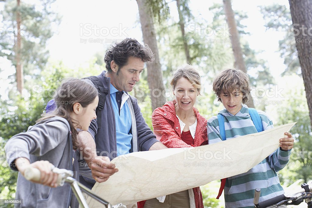 Family looking at map in woods royalty-free stock photo