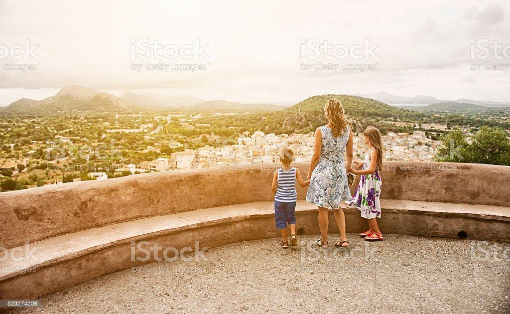 Family looking at mediterranean town of Pollenca, Mallorca. stock photo