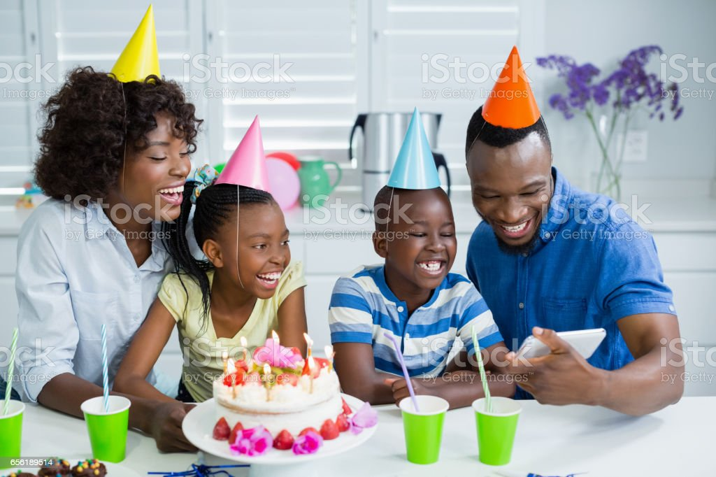 Family looking at picture while celebrating birthday party stock photo