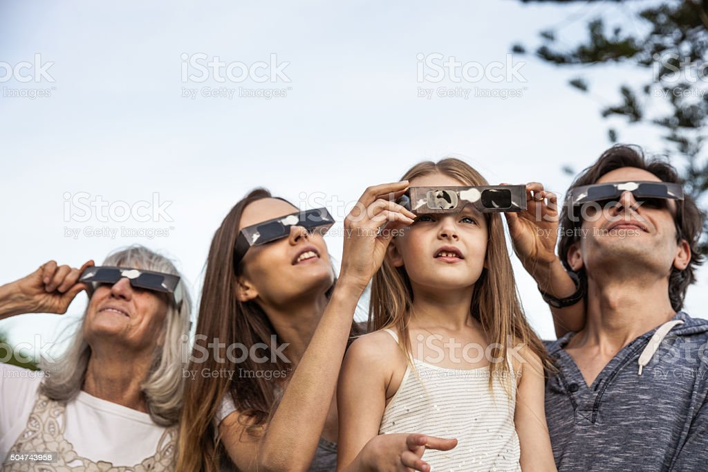 Family looking at Solar Eclipse using solar glasses stock photo