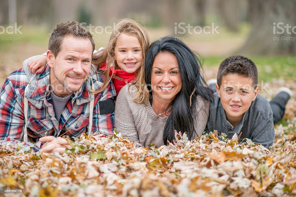 Family Lying in a Pile of Leaves stock photo