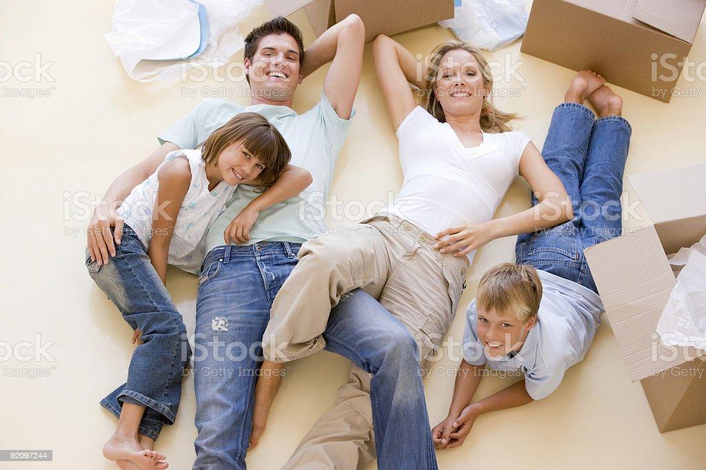 Family lying on floor in new home stock photo