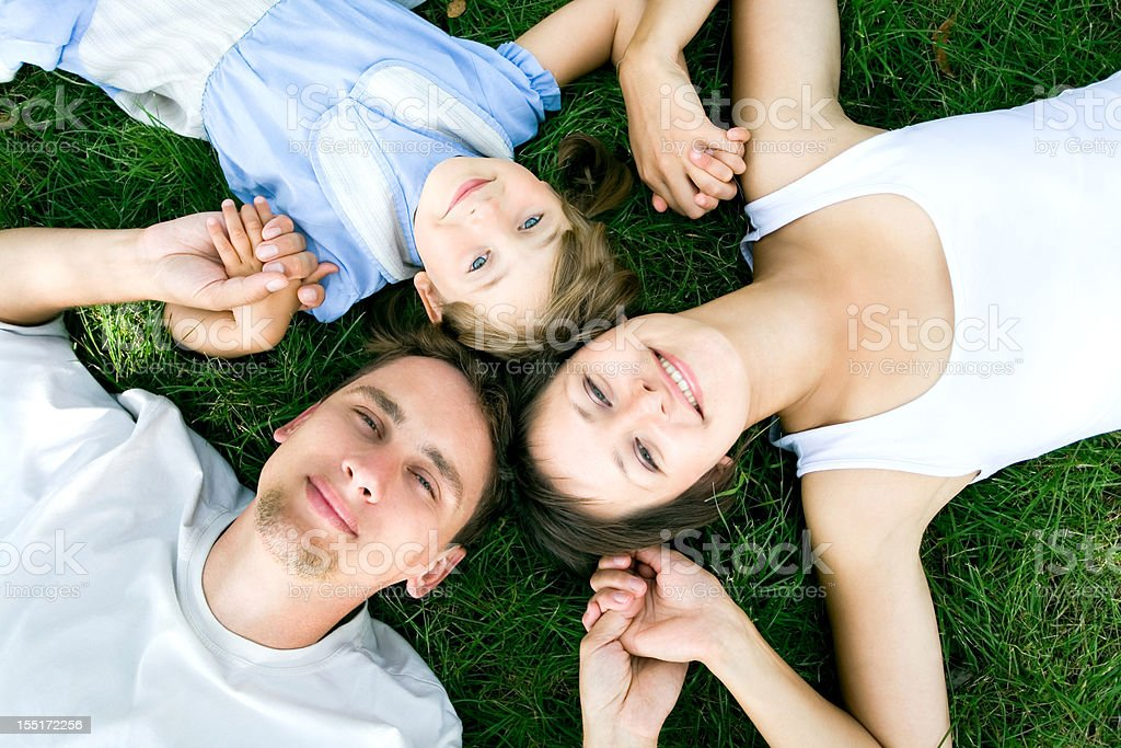 Family lying on grass holding hands royalty-free stock photo