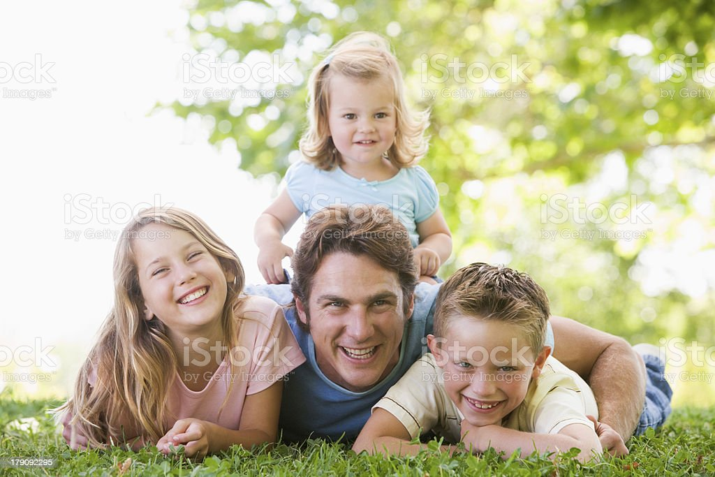 Family lying outdoors smiling royalty-free stock photo