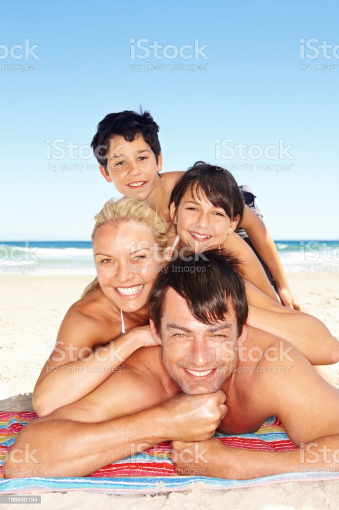 Family lying stacked on one another on the beach royalty-free stock photo