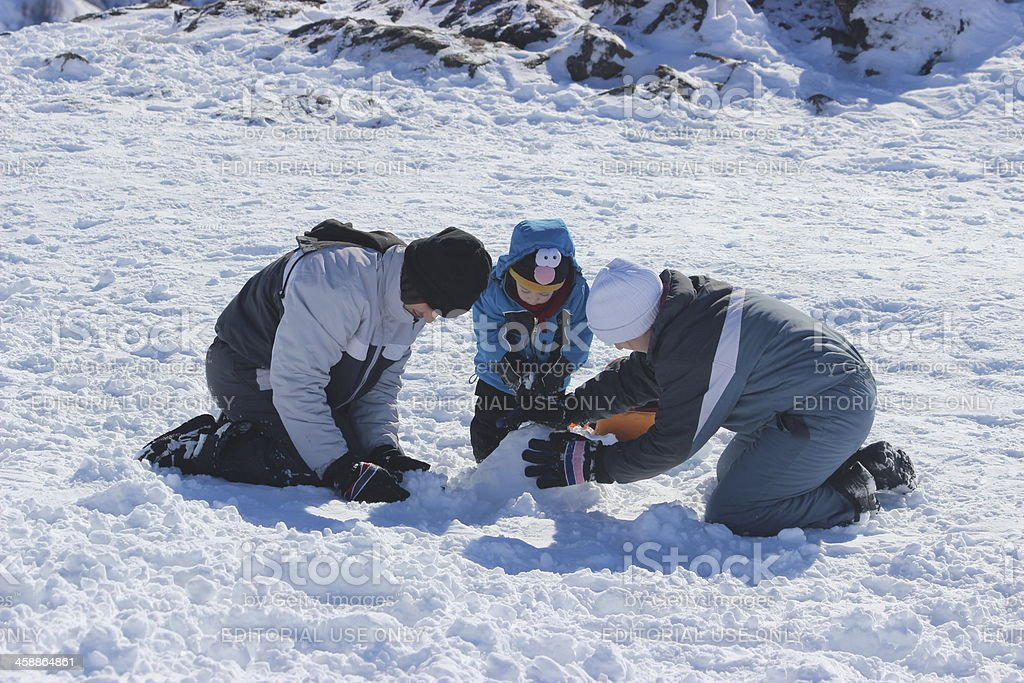 Family making a snowman at Andes mountains 3 royalty-free stock photo