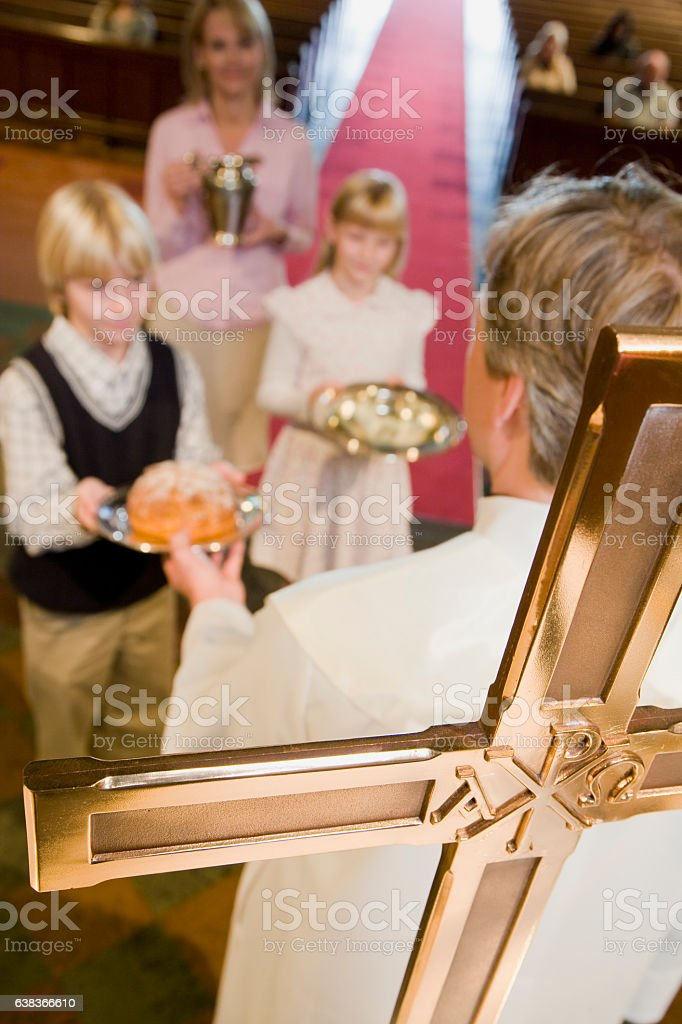 Family making offering at mass in church stock photo
