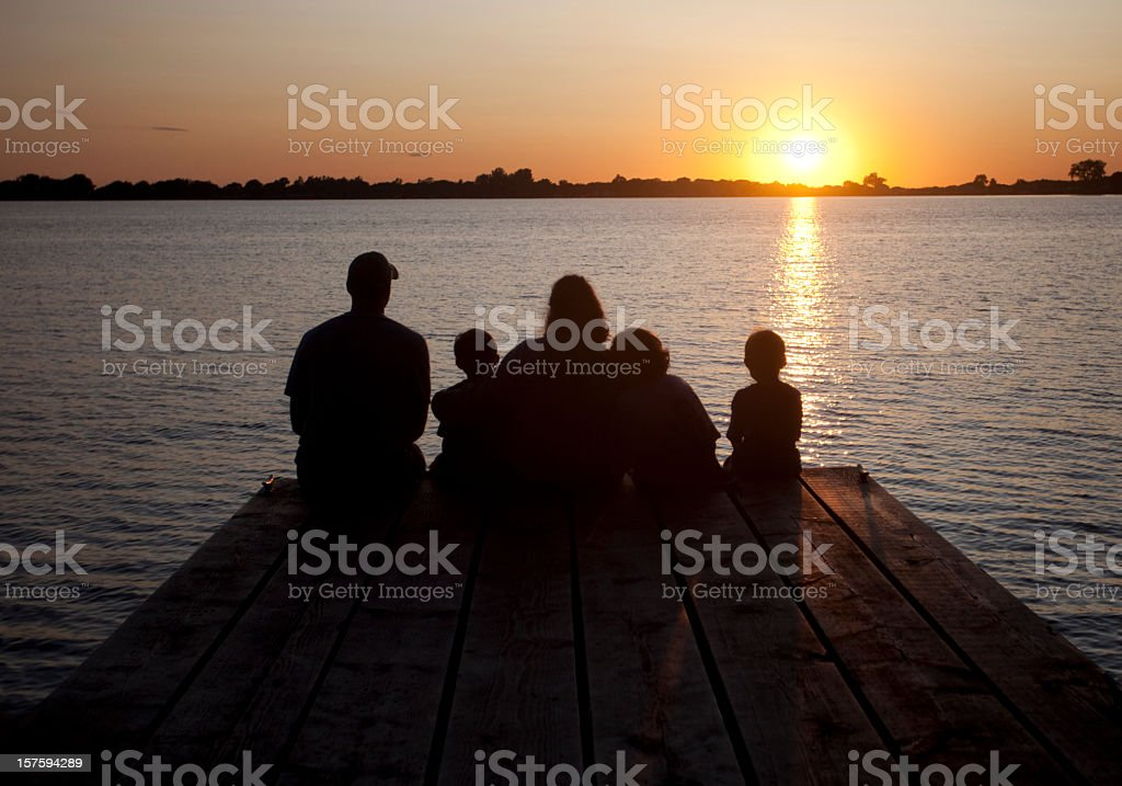 Family moment on a wooden dock by the lake royalty-free stock photo