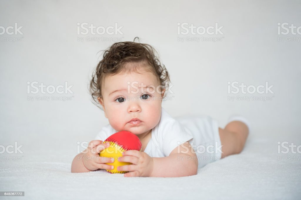 Family Moments- Baby boy lying on front and playing stock photo