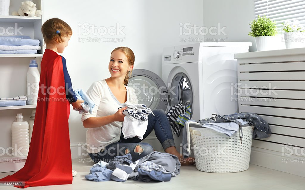 family mother and child little superhero helper in laundry room stock photo