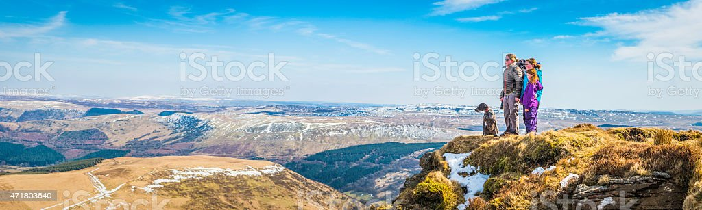 Family mother children hiking on mountain summit overlooking panoramic landscape stock photo