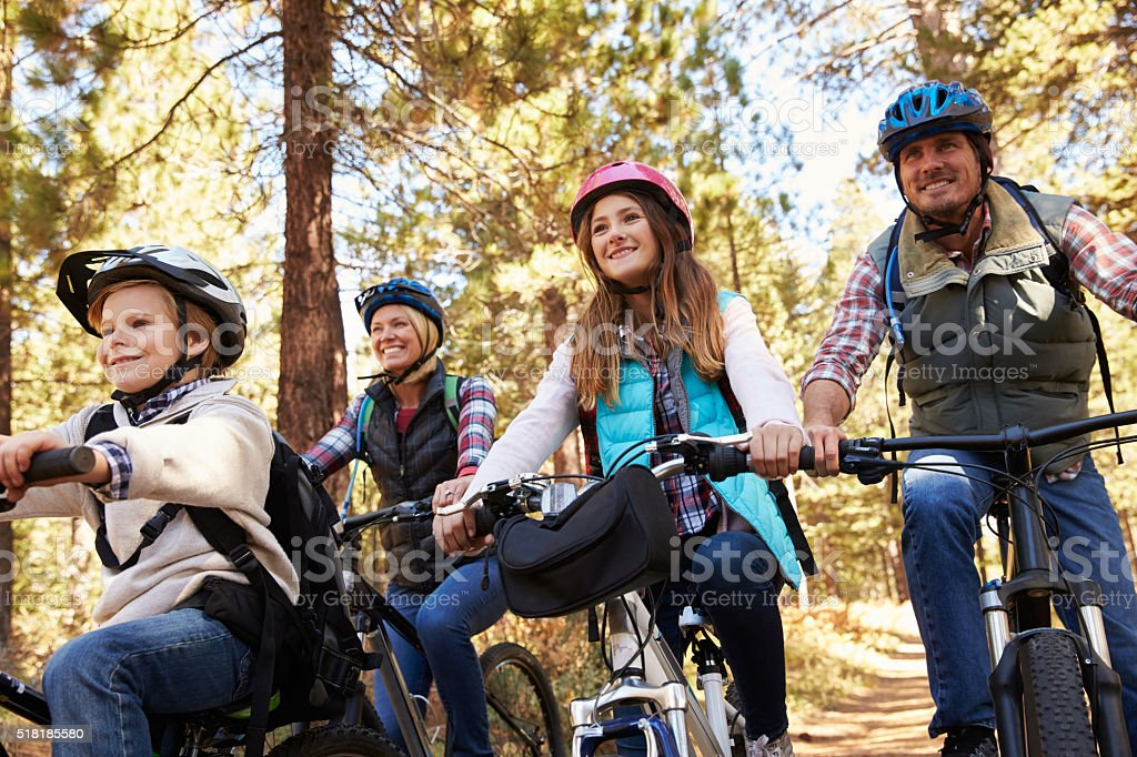 Family mountain biking in a forest, low angle front view stock photo