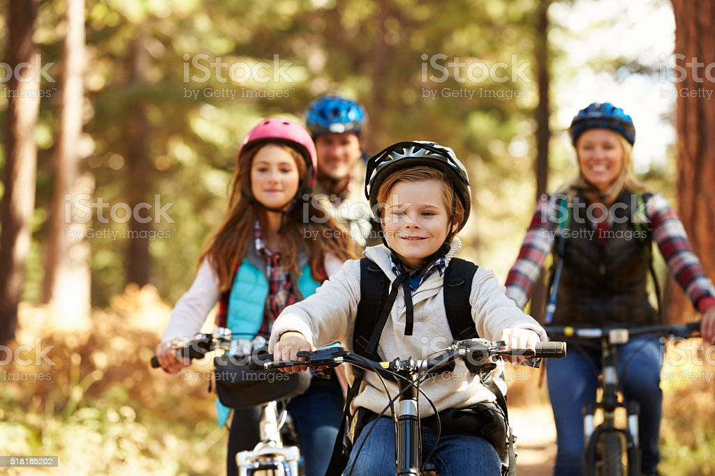 Family mountain biking on forest trail, front view, close-up stock photo