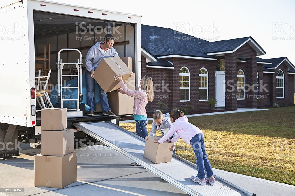 Family moving house, unloading truck stock photo
