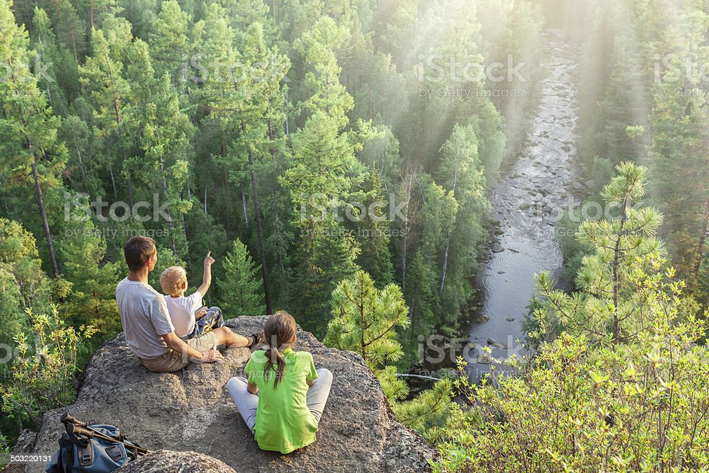 Family of backpackers look at beautiful view stock photo