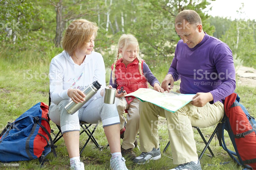 Family of backpackers taking coffee break royalty-free stock photo