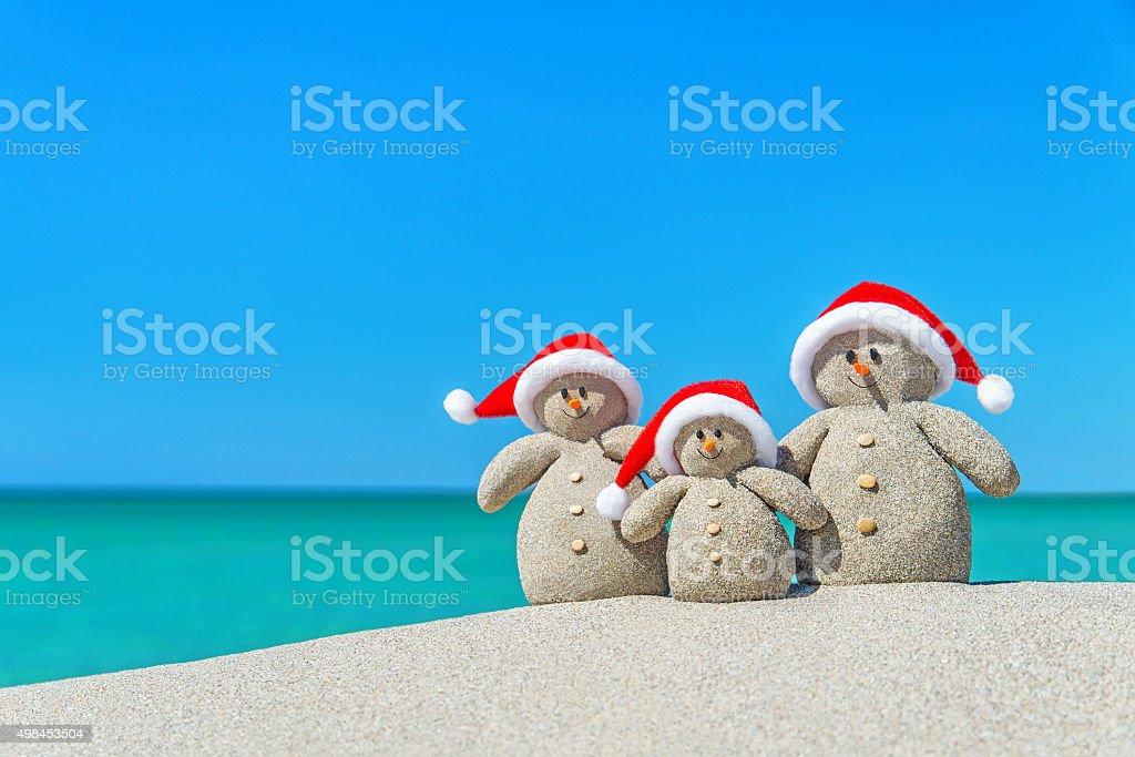 Family of Christmas Snowmen in santa hats at tropical beach. stock photo