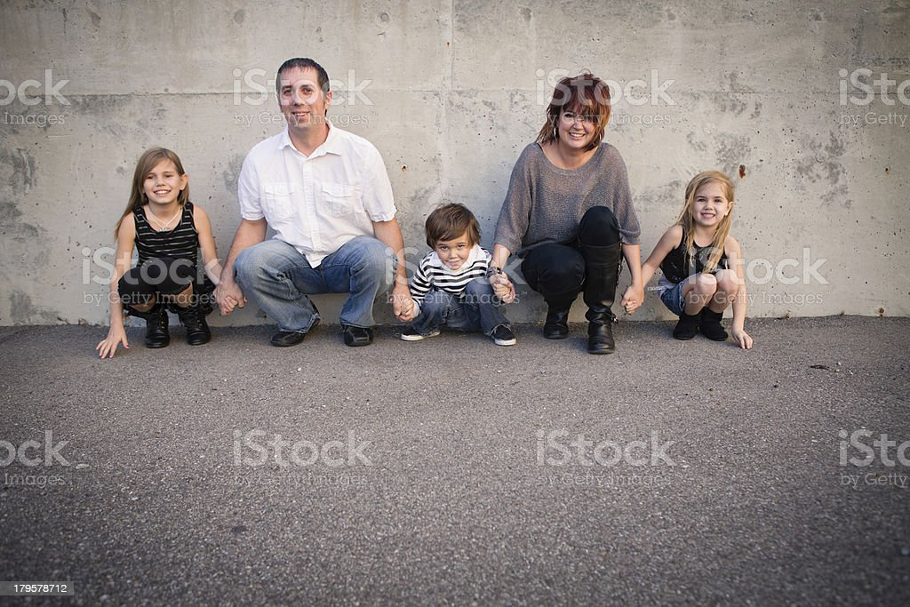 Family of Five Crouching By Concrete Wall royalty-free stock photo
