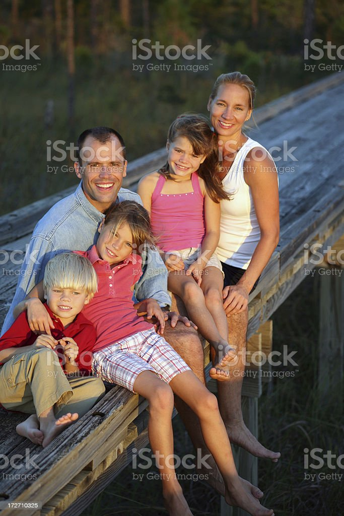Family of Five sitting on Dock royalty-free stock photo