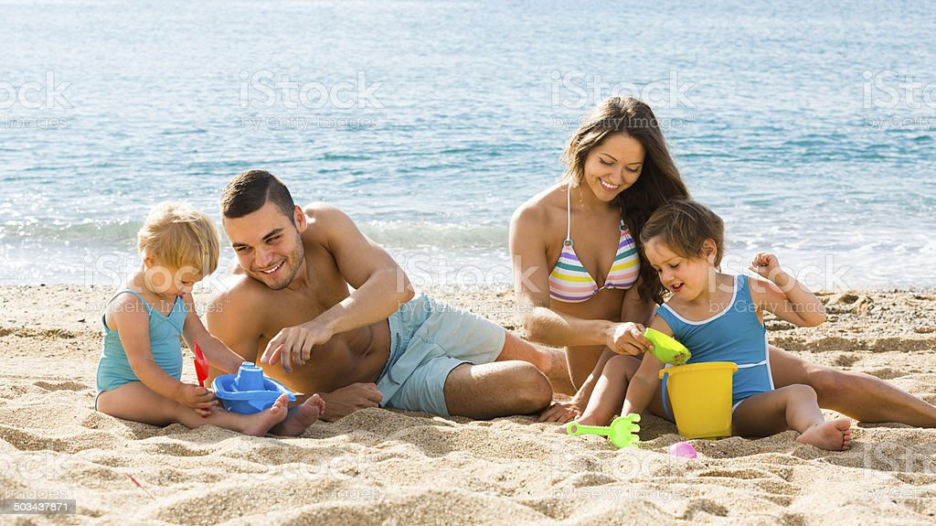 Family of four at the beach stock photo