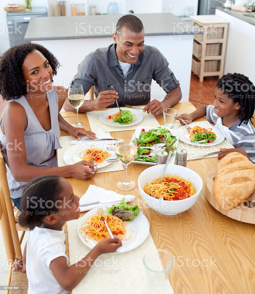 Family of four at the table together eating pasta and salad  stock photo