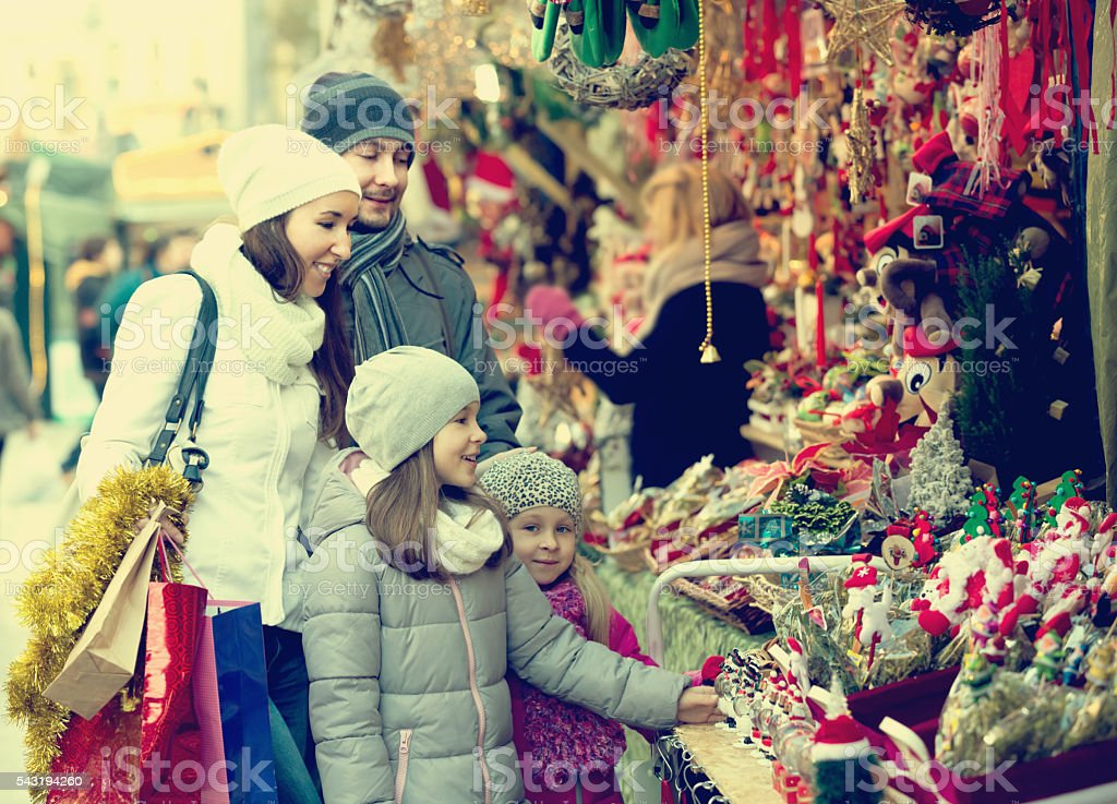 Family of four buying handmade decorations stock photo